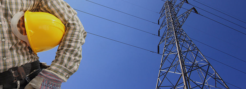 electrician holding a hard hat standing in front of an electrical tower